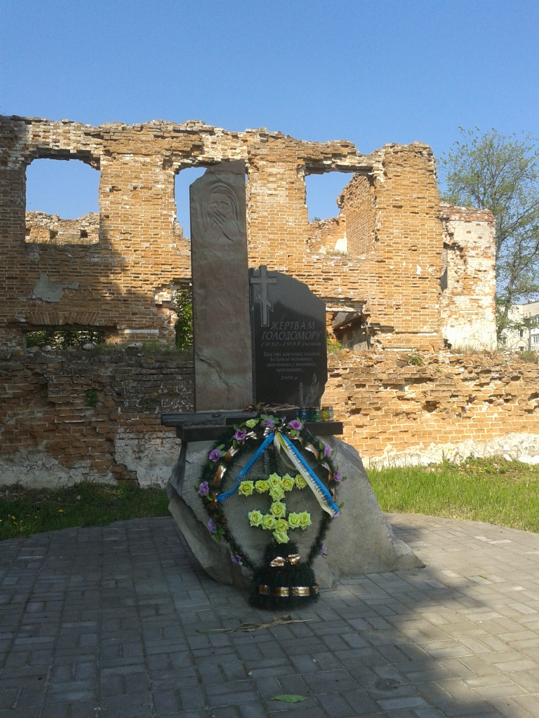 Пам'ятник жертвам голодомору на тлі руїн в'язниці