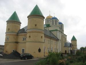 На початку XVII століття до храму (нині з синіми та золотою банею) добудовано келії з оборонними вежами (зелені конусоподібні дашки)